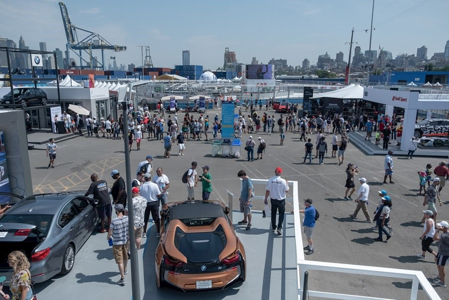 a crowd of people visit various stalls at a Formula E E-Prix