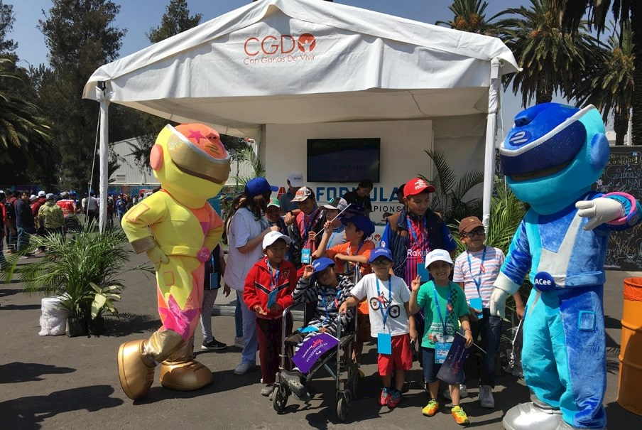 kids play with dressed up performers at a Formula E community engagement event in Mexico
