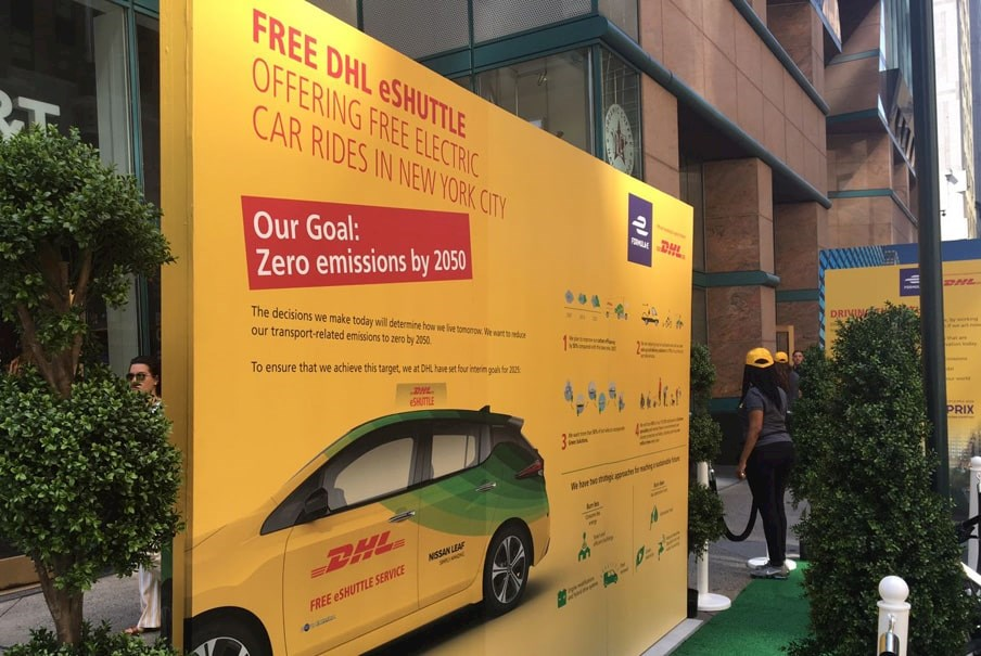 information board showing DHL's electric shuttle service at a Formula E event