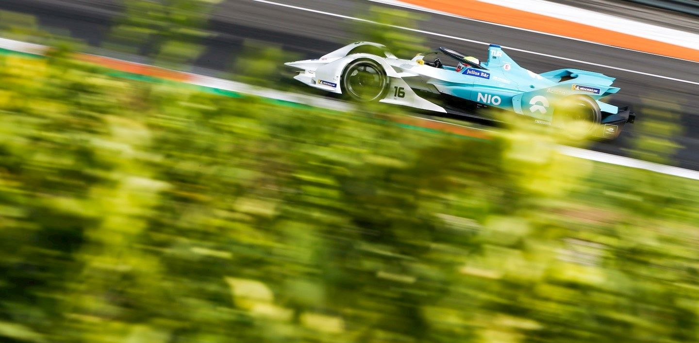 a Generation 2 Formula E racing car drives past green bushes - Formula E sustainability