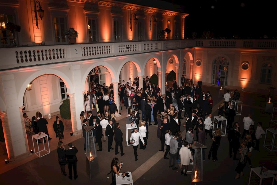 attendees of a Formula E charity event gather in a lit up courtyard