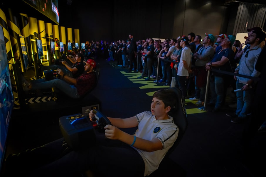 fãs guiando na Gaming Zone do Allianz E-Village na E-Race