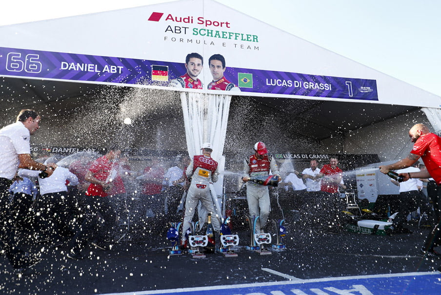 Formula E racing drivers Daniel Abt and Lucas Di Grassi being sprayed with champagne