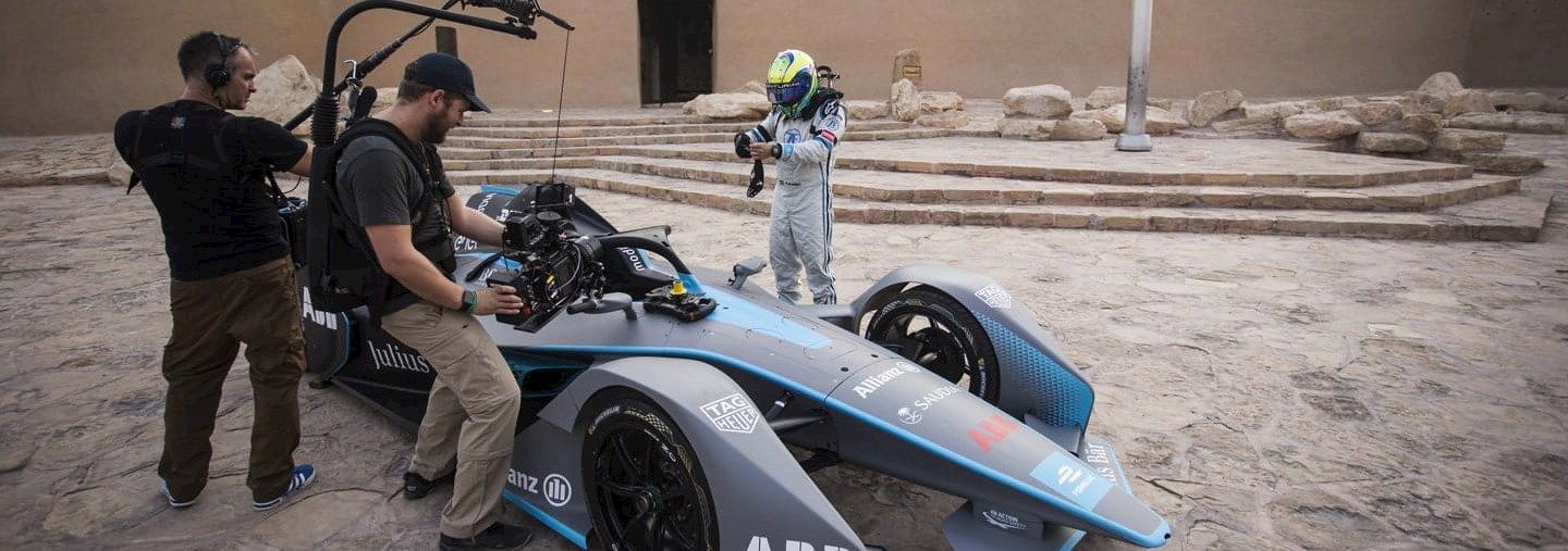 a film crew records a formula e driver approaching a racing car